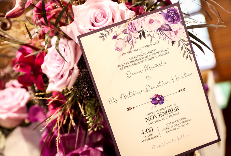 Wedding photography, a purple wedding invitation sits on a bouquet of lavender roses and greenery.