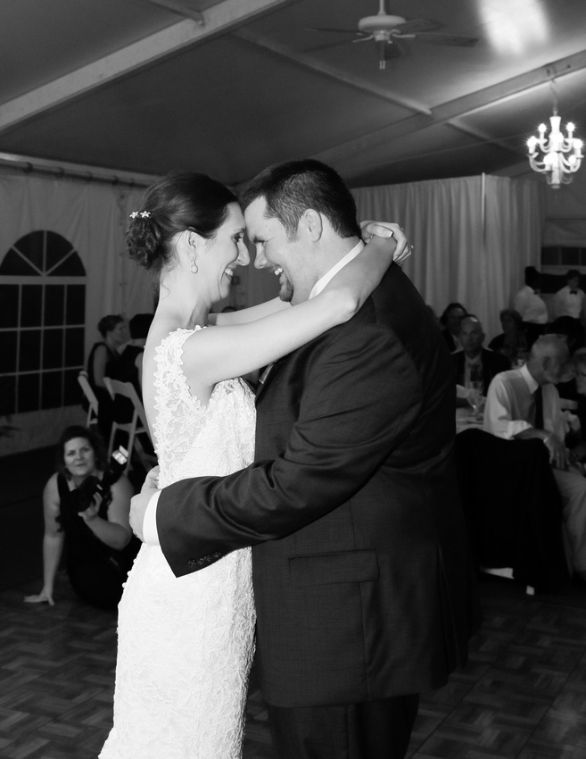 Wedding photography, a bride and groom stand face to face on the dance floor smiling. They have their arms around each other.