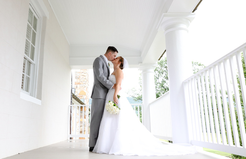 Wedding photography, a bride and groom share a romantic kiss on a white porch with trees behind them.