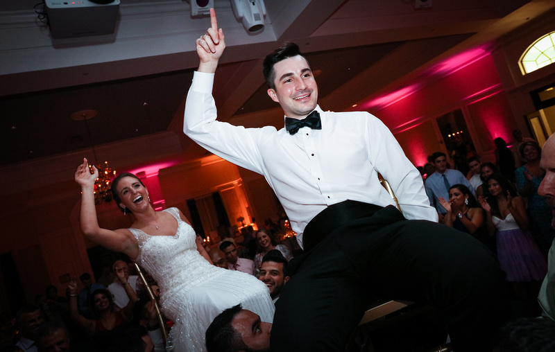 Wedding photography, a bride and groom celebrate while being lifted up on chairs.