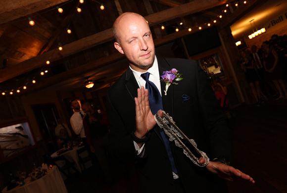 Wedding photography, the groom playfully looks at the camera as he preps to toss the garter.