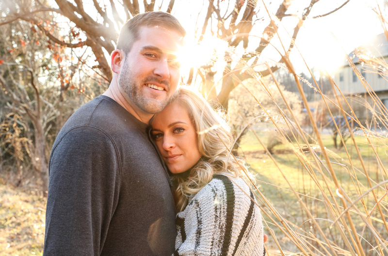 Engagement photography, a couple looks at the camera calmly as they stand by tall cattails. The sun flares behind them.