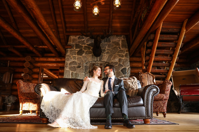 Wedding photography, a bride and groom lounge by the stone fireplace on a leather couch.