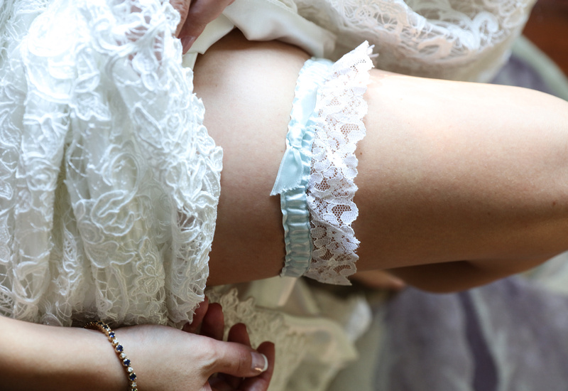 Wedding photography, a close up shot of a bride's thigh wearing a white lace and baby blue garter.
