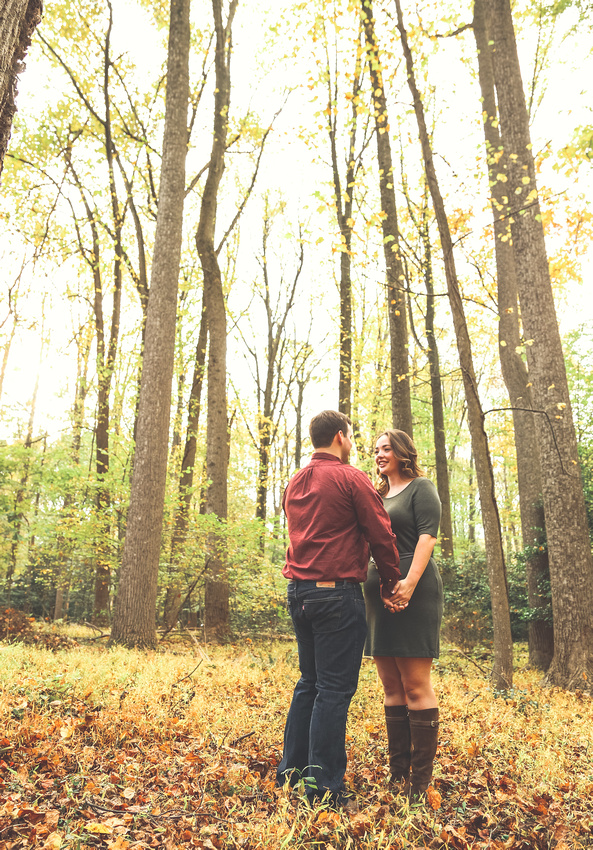 Engagement photography: a young couple in the woods holds hands next to tall trees.