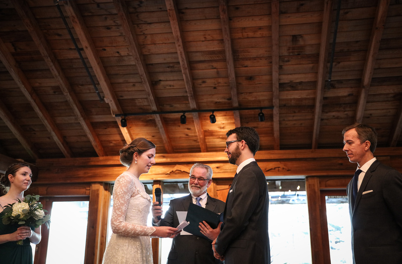 Wedding photography, a bride in a lace gown says her vows in a log cabin.