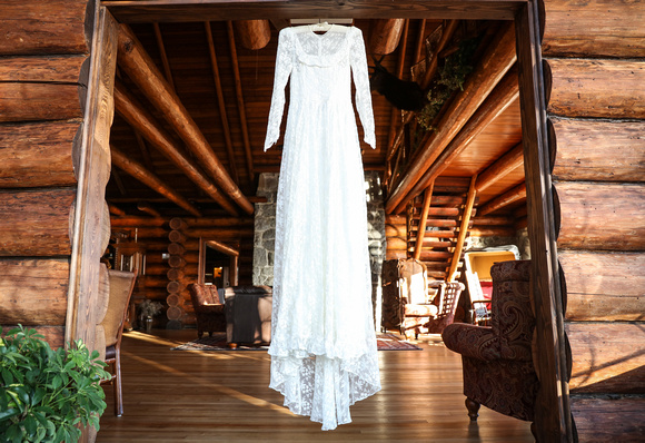 Wedding photography, a lace wedding dress hangs in the doorway of a log cabin.