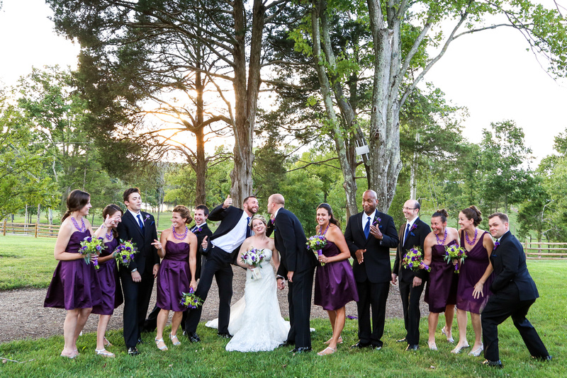 Wedding photography, a wedding party gets silly standing in front of tall trees.