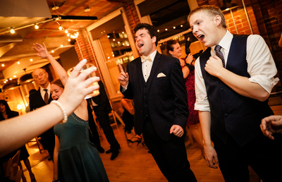 Wedding photography, a groom sings his heart out while dancing with friends.