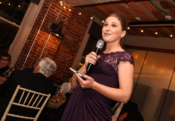 Wedding photography, the maid of honor in a purple dress laughs while giving a speech.