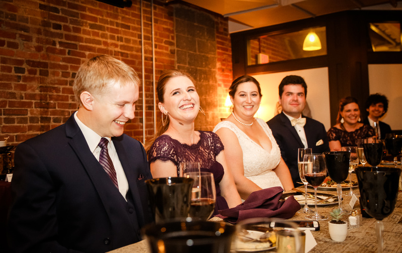 Wedding photography, the wedding party laughs while listening to speeches at dinner.