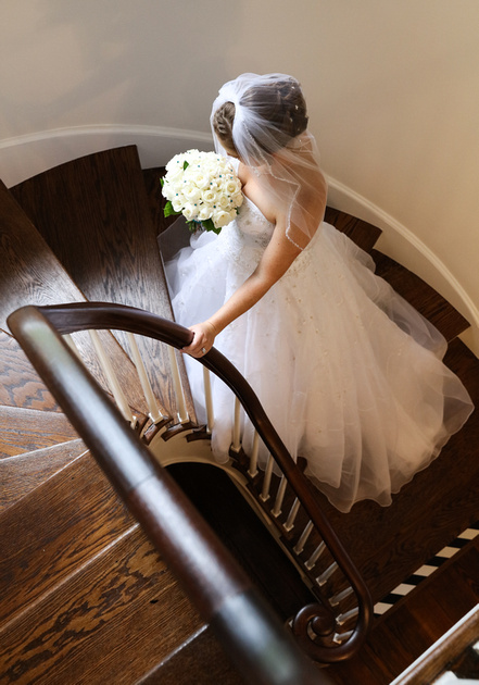 Wedding photography, a bride stands on a curved wooden stairwell with her hand on the railing, looking down at her flowers.