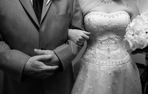 Wedding photography, a bride and her father stand arm in arm before the ceremony.