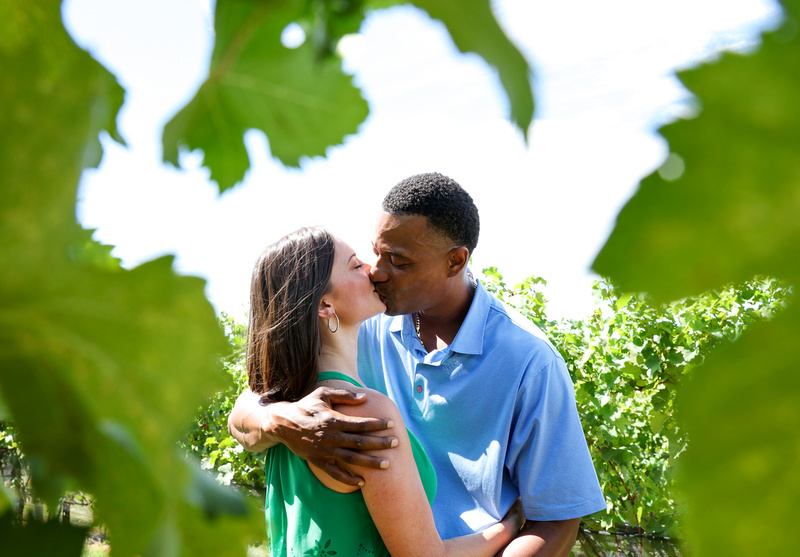 Engagement photography: a couple is seen through the green vineyard leaves, kissing romantically.