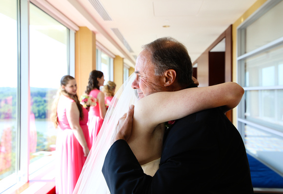 At front of a long corridor, a serene-looking father tightly hugs his daughter, the bride. 5 reasons you need to click with your photographer.