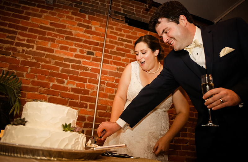 Wedding photography, a bride and groom cut their cake.