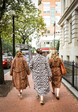 Wedding photography, a bride and bridesmaids walk down the DC streets wearing animal print robes.