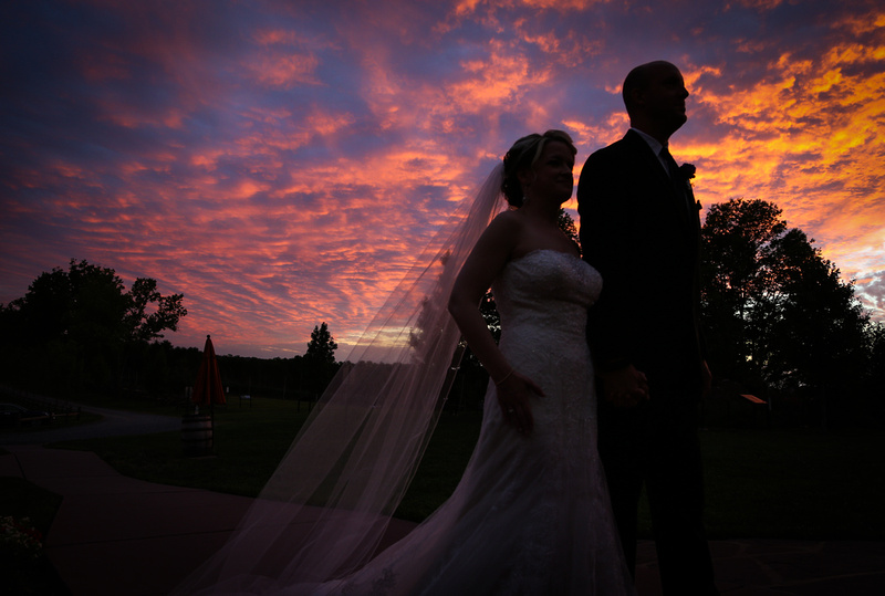 Wedding photography, a bride and groom enter their reception in silhouette with a gorgeous sunset behind them.