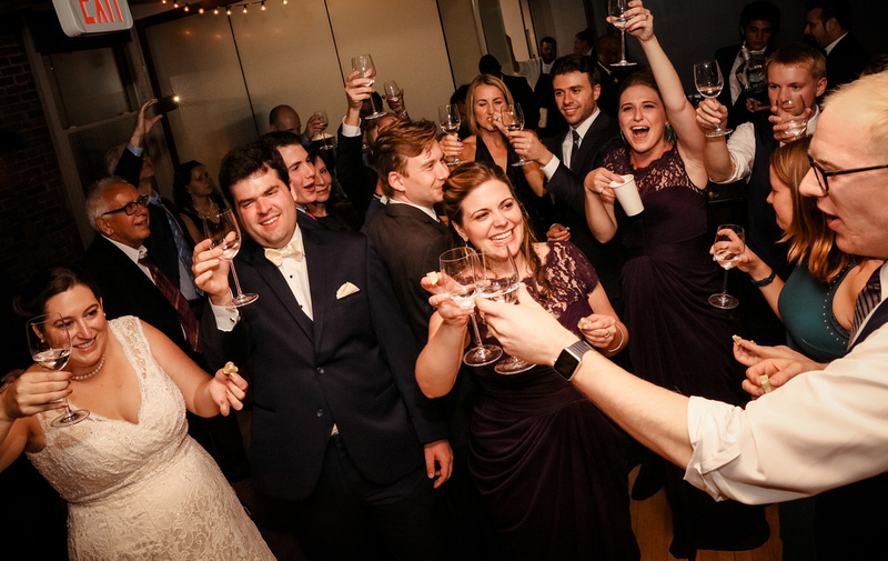 Wedding photography, happy wedding guests raise a glass and share a shot.