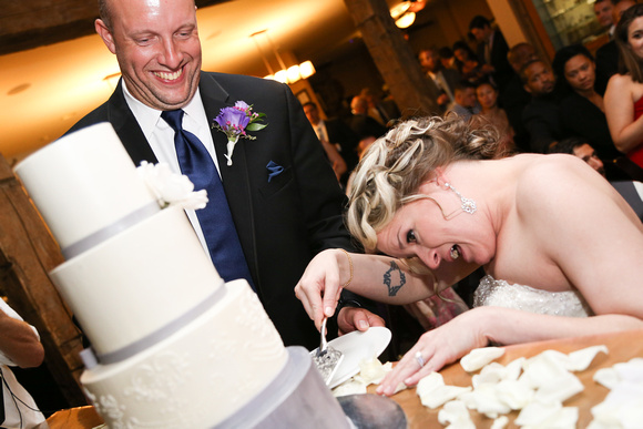 Wedding photography, the groom laughs as he watches his silly bride cut the cake.