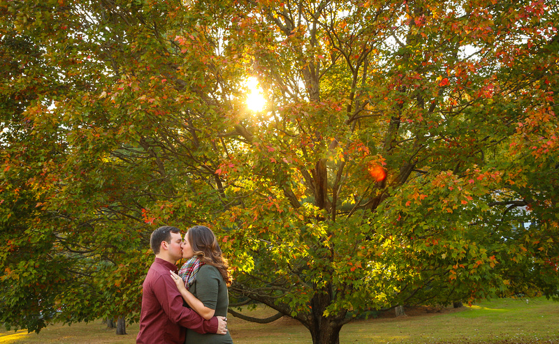 Engagement photography: a young couple kisses while standing in front of a beautiful fall tree.