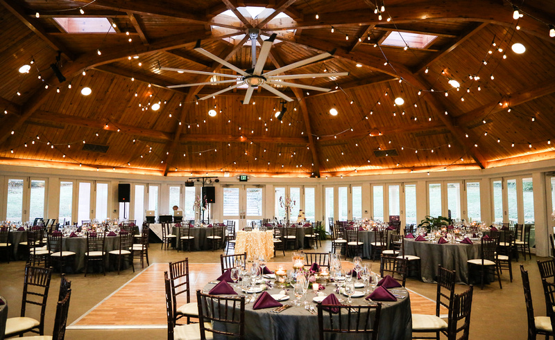 Wedding photography, the reception hall with a gorgeous wooden ceiling and string lights.