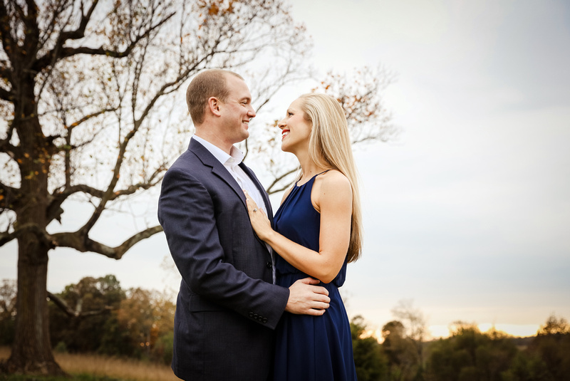 Engagement photography, a young lady in a blue dress and man in a navy blazer embrace.