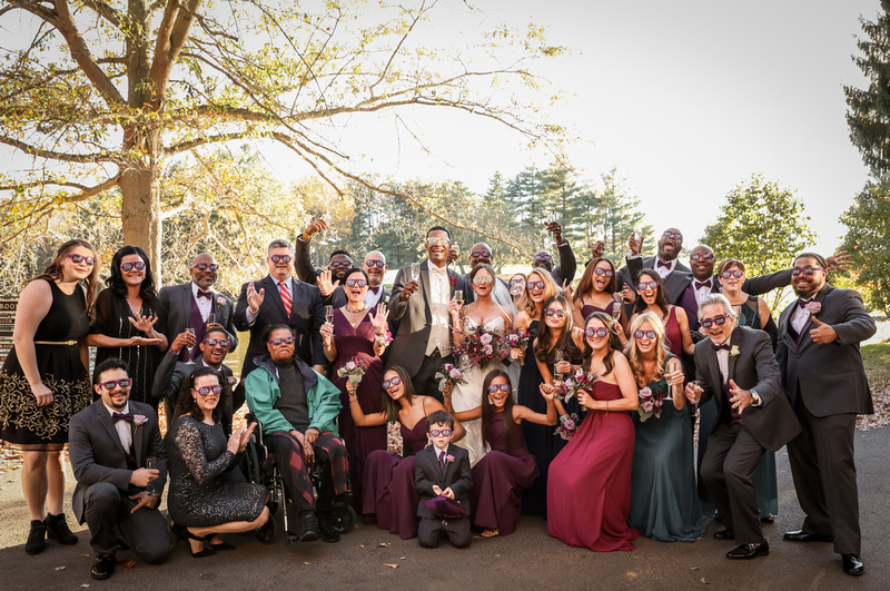 Wedding photography, a group celebrates with a toast and purple bride and groom sunglasses.