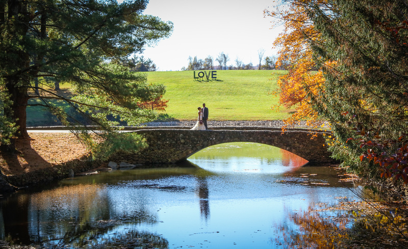 Wedding photography, a bride and groom stand on a stone bridge. A sign reading love is on the hill behind them.