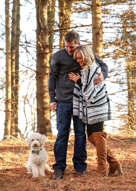Engagement photography, a couple stands together in the woods looking down at their small white dog.