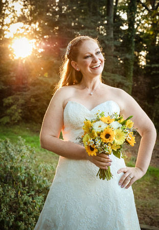 Wedding photography, a bride laughs with the sun shining through the trees behind her.