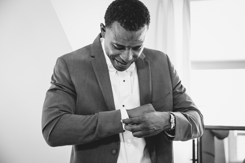 Wedding photography, a black and white image of a groom putting on his cufflinks.