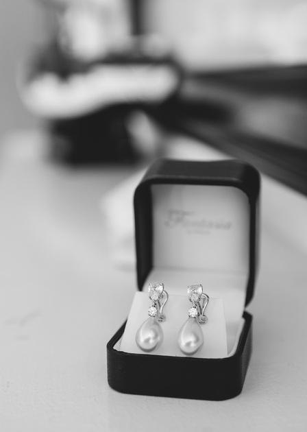 Wedding photography, teardrop diamond earrings in a black jewelry box.
