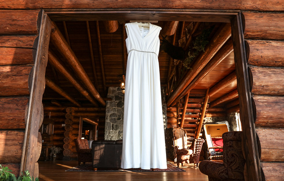 Wedding photography, a wedding dress hangs in the doorway of a log cabin.