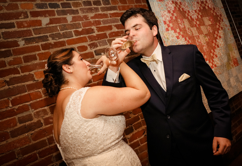 Wedding photography, a bride and groom link arms and drink a champagne toast.