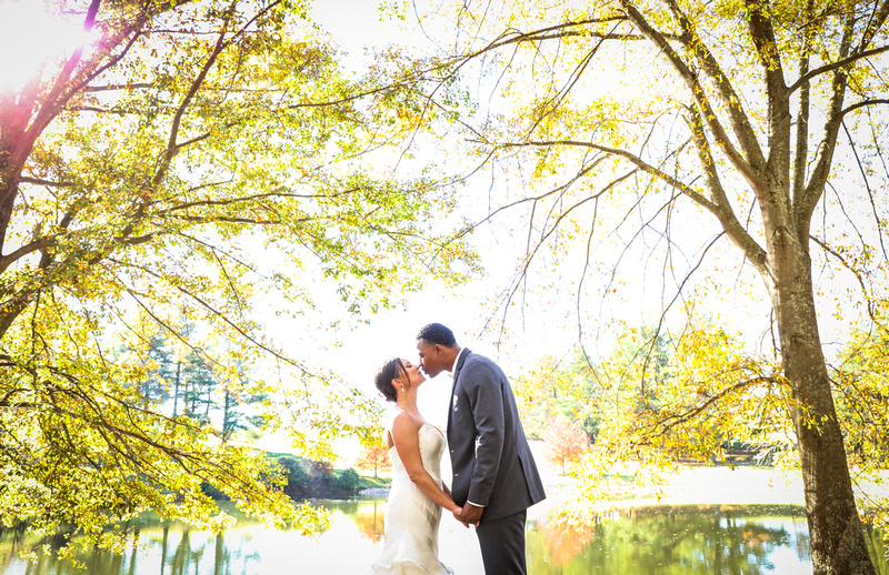Wedding photography, a bride and groom kiss between two yellow trees and a lake.