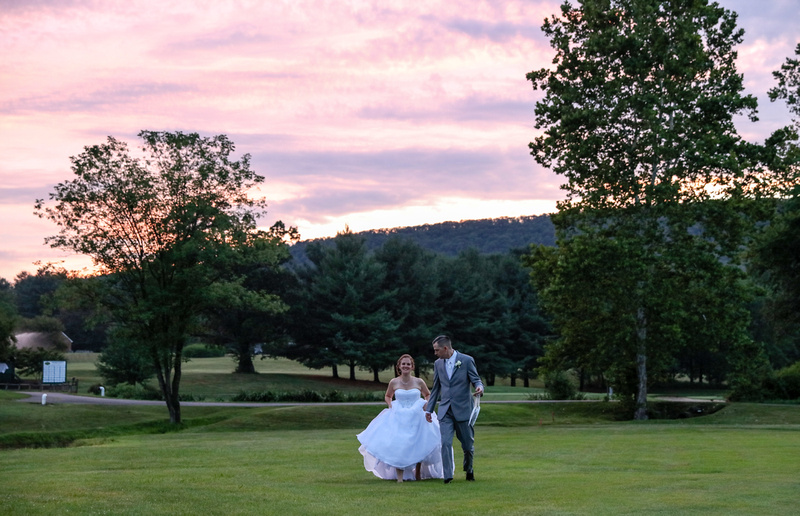 Wedding photography, a bride and groom walk across an open field at sunset. She holds up her dress as they walk.