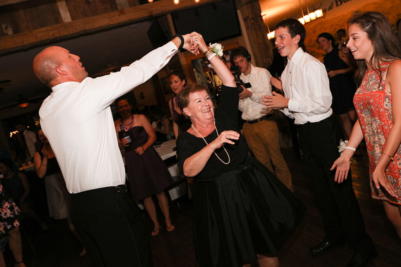 Wedding photography, the groom dances with the mother of the bride who is smiling.
