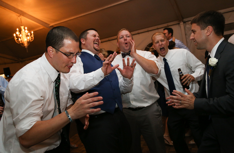 Wedding photography, a groom and his groomsmen dance and sing with beers.
