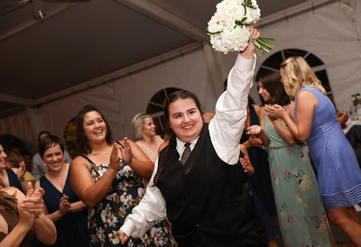 Wedding photography, a young girl in a white shirt and black vest holds up the bouquet triumphantly.