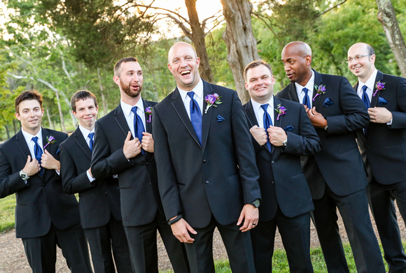Wedding photography, a groom laughs heartily, flanked by his groomsmen in black suits with blue ties.