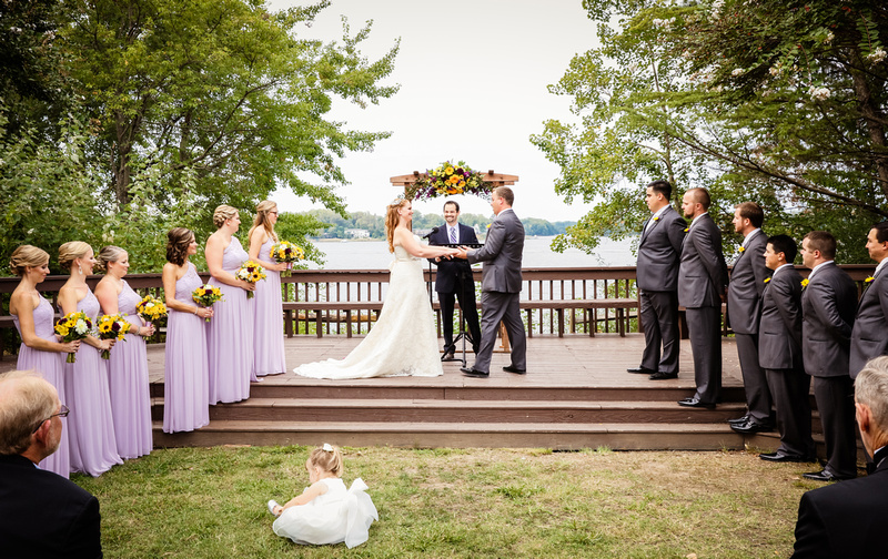 Wedding photography, the ceremony is waterfront with the bride and groom holding hands on the deck.