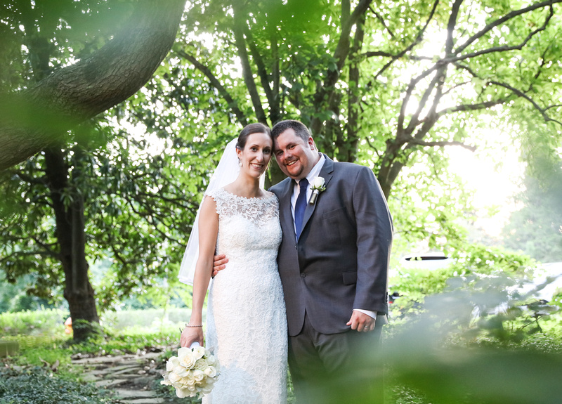 Wedding photography, bride and groom embrace and smile at the camera. They are surrounded by green trees.