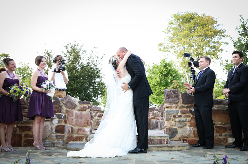 Wedding photography, a bride and groom share their first kiss as the wedding party smiles on.