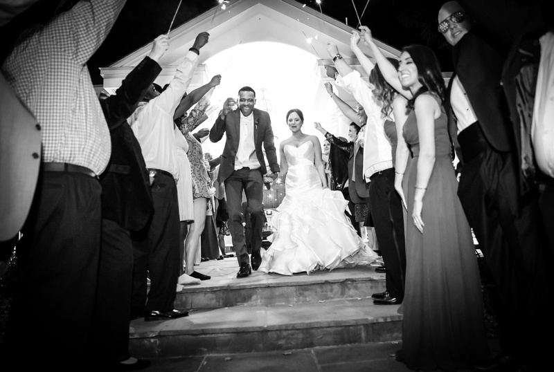 Wedding photography, a black and white image of the bride and groom running under a tunnel of sparklers.