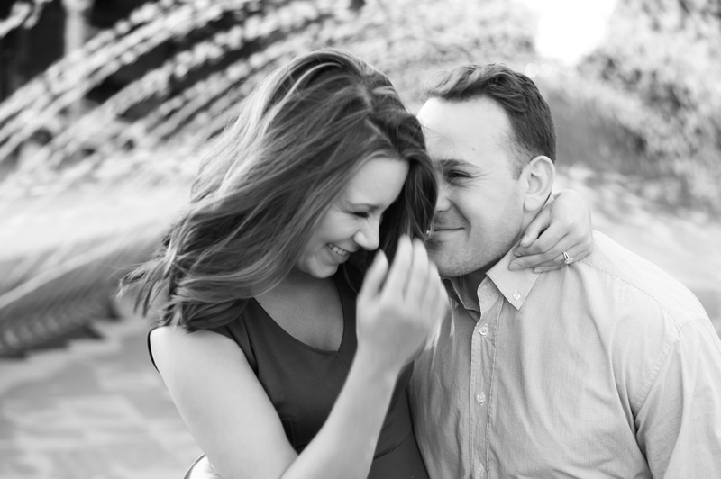 A young woman laughs with delight as her fiancé whispers in her ear.