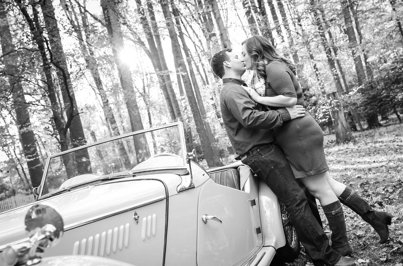 Engagement photography: two fiancées lean against an antique car and kiss.