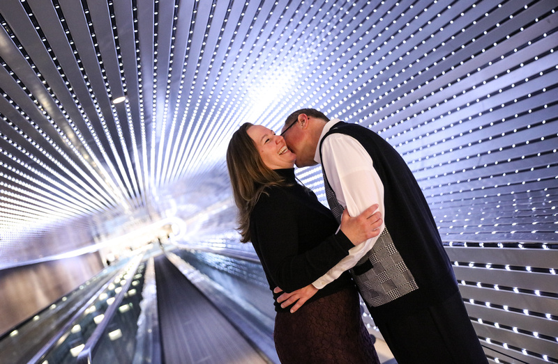 Engagement photography, a man kisses a women's neck as she laughs. They are in a light tunnel.