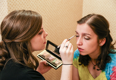 Wedding photography, the maid of honor does eye makeup for a bridesmaid in a tie dye tee.