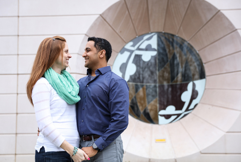 Engagement photography, a couple smiles at each other in front of a window with the Maryland flag symbol on it.